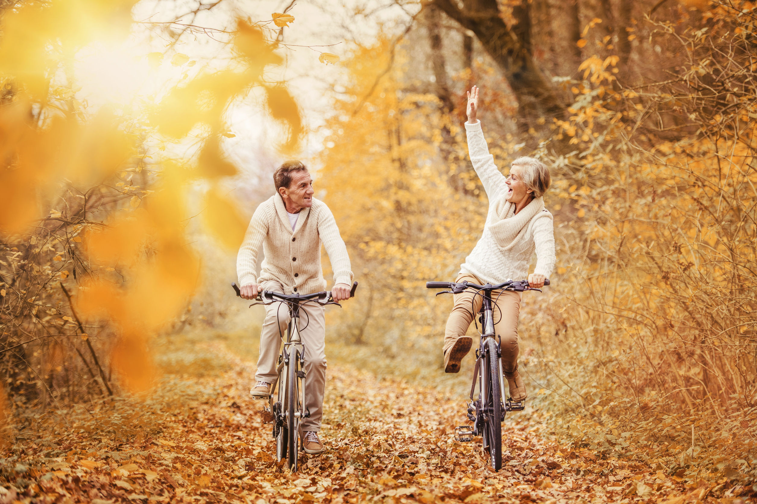 active seniors ridding bike in autumn nature. they having fun outdoor.